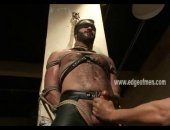 Rugged man is bound in leather and blindfolded by a dominating man that hits his chest and plays with his nipples also jerking him off painfully slow