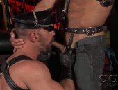 Heavy beef Kristian Alvarez and Scott Carter in a dungeon play wearing leather caps and chaps with studs.