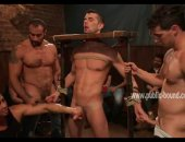 Gorgeous man is bound in a medieval device, tied up and forcefully jerked off by dominatig men at a party while he, himself jerks off two other men
