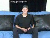 Lonely straight boy in cap sit on sofa to tell you about himself.