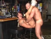 huky dude throws his legs in the air for a bear to lay it in him over a bar stool