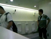 Cute Japanese guy pulls out his cock and beats off in a public restroom. Older guy jerks it for him.