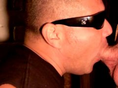 mature dude with shades on blowing a fatty through a glory hole