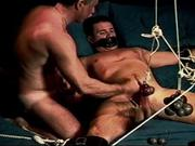 My hot bottom dude is really muscular with big legs and big cock. I have him restrained and gagged and I add more and more weights which pull a rope over a pulley and pull on his testicles which are attached. I jack him off as he asks for more weights to be added.